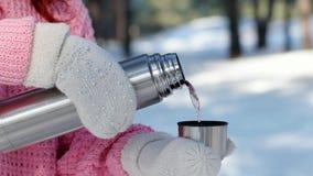 Frau gießt heißes Getränk von einer Metallthermosflasche, Hand in gestrickten Handschuhen gießt Tee in eine Schale, Thermosflasch stock video