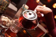 Frau gießt Tee Lizenzfreie Stockfotos
