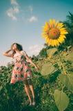 Frau glücklich auf dem Sonnenblumenblumengebiet Lizenzfreie Stockfotografie