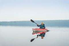 Frau glücklich, vom roten Kajak auf ruhigem See zu schaufeln Stockbilder
