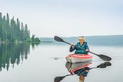 Frau glücklich, vom roten Kajak auf ruhigem See zu schaufeln Stockfotografie