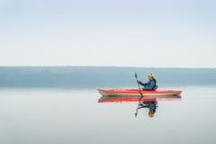 Frau glücklich, vom roten Kajak auf ruhigem See zu schaufeln Stockfotos
