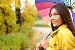 Frau glücklich mit Regenschirm unter dem Regen Stockfotografie
