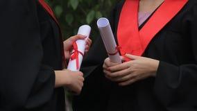 Frau graduiert in den akademischen Kleidern, die Diplome halten und über Zukunft sprechen stock video footage