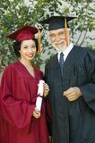 Frau-graduiertes haltenes Zertifikat mit Dekan Lizenzfreie Stockfotos