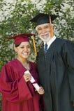 Frau-graduiertes haltenes Zertifikat mit Dekan Stockfotos