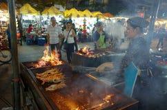 Frau grillt Garnelen am Nachtmarkt Lizenzfreies Stockfoto
