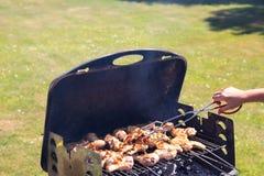 Frau grillt Hühnerfleisch und benutzt Grillzangen Konzept lizenzfreie stockfotografie
