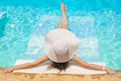 Frau in großem whire Hut, der auf dem Swimmingpool sich entspannt Stockfoto