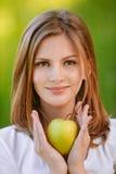 Frau hält Apfel an lizenzfreie stockbilder