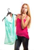 Frau hält Bluse und Zweifel, um zu kaufen oder nicht Stockfotos