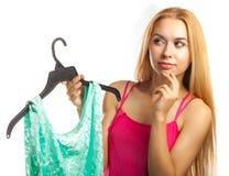 Frau hält Bluse und Zweifel, um zu kaufen oder nicht Lizenzfreies Stockbild