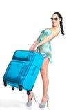 Frau hält den schweren Reisenkoffer an Stockfoto