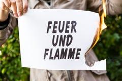 Frau hält ein brennendes Papier mit deutschem Text Stockfotografie
