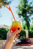 Frau hält ein exotisches Cocktail außerhalb des Hotels lizenzfreie stockfotografie