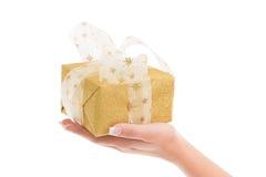Frau hält ein lokalisiertes goldenes Geschenk für Weihnachten in den Händen Lizenzfreie Stockbilder