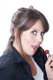 Frau hält eine Kirsche nahe ihrem Mund an Stockfoto