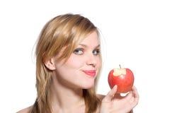 Frau hält einen roten Apfel an, den in gebissen worden ist Lizenzfreie Stockfotografie