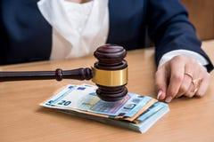 Frau hält hölzernen Hammer über Banknoten in den Euros lizenzfreie stockfotografie