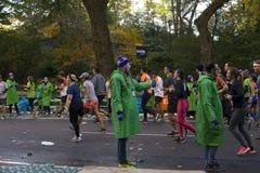Frau hält heraus Wasser zu den Läufern, die an NYC-Marathon teilnehmen stockbild