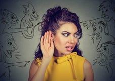 Frau hält ihre Hand nahe Ohr und hört sorgfältig auf schlechte Stimmen Lizenzfreie Stockfotografie
