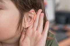 Frau hält ihre Hand nahe Ohr und sorgfältig hören stockfoto