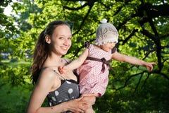 Frau hält Kind an Stockfotografie