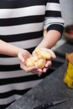 Frau hält potatos in ihren Händen an Stockbild