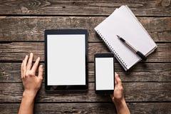 Frau hält Smartphone mit Tablette Stockfoto