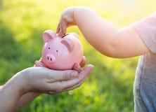 Frau hält Sparschwein, während Baby Münzen nach innen setzt stockfotografie