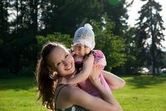 Frau hält Tochter an Stockfoto
