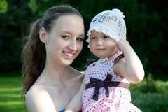 Frau hält Tochter an Stockbild