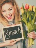 Frau hält Tulpen, Brett mit Text am 8. März Stockbilder