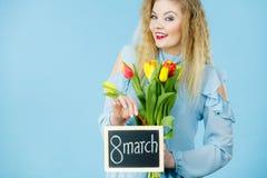 Frau hält Tulpen, Brett mit Text am 8. März Lizenzfreies Stockbild