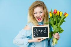 Frau hält Tulpen, Brett mit Text am 8. März Stockfotos