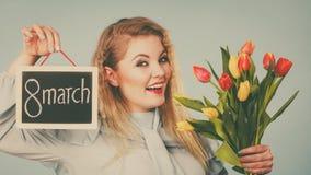Frau hält Tulpen, Brett mit Text am 8. März Lizenzfreies Stockfoto