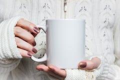 Frau hält weißen Becher in den Händen Design-Modell für Winterurlaube Lizenzfreie Stockbilder