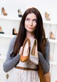 Frau hält zwei Schuhe im Einkaufszentrum Lizenzfreies Stockbild