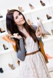 Frau hält zwei Schuhe im Einkaufszentrum Lizenzfreies Stockfoto