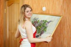 Frau hängt Abbildung auf Wand zu Hause Stockfoto