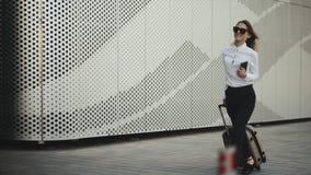 Frau haben einen Anruf mit ihrem Gepäck am Flughafen stock video