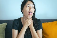 Frau haben Halsschmerzen, ein weibliches krankes und ein Berühren ihren Hals mit der Hand, Gesundheitswesen-Konzepte stockfoto