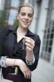 Frau halten Schlüssel an der Kamera Stockfotografie