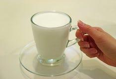Frau ` Hand, die eine Schale warme Büffel-Milch hält, diente in der transparenten Glasschale Lizenzfreie Stockfotografie