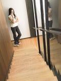Frau am Handy unten der Treppe Stockbilder