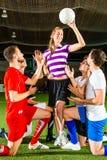 Frau hat einen Fußball in der Hand, die Männer, die unten knien Stockbild