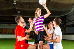 Frau hat einen Fußball in der Hand, die Männer, die unten knien Lizenzfreie Stockfotos