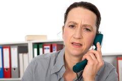 Frau hat einen unangenehmen Telefonanruf Stockbild