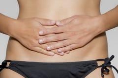 Frau hat ihre Hände auf ihrem Magen Stockbilder