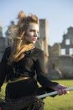 Frau am Hexenkostüm auf Ruinenhintergrund Stockfoto